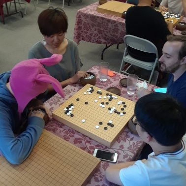 Four Go players, one in a bunny hat, playing a team game of Rengo