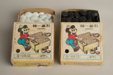 White and black Go stones in cardboard box decorated with an iconic rodent.