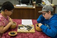 A girl and a boy studying their game of Go moves