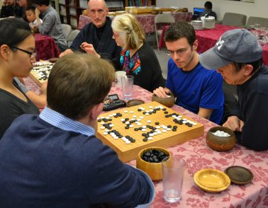 Go players gaze fiercely at the board in the early midgame.
