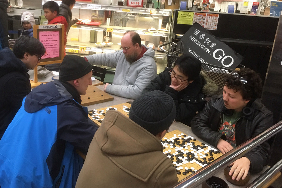 Smiling Go players face each other for casual and teaching games in a food court.